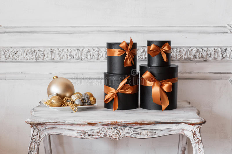 Wrapped gift black boxes with ribbons as Christmas presents on a table luxury white wall design bas-relief stucco stock photos