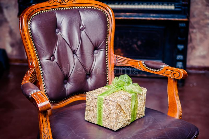 Wrapped gift boxes with ribbons as Christmas presents on a leather chair. christmas gift on vintage chair.Happy new year with royalty free stock images