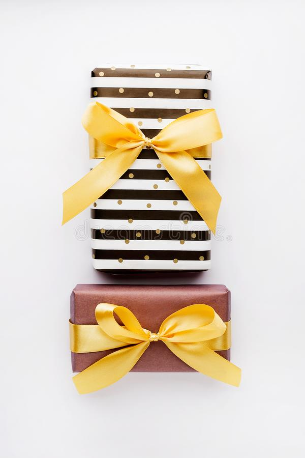 Wrapped gifts in black and white,purple paper,golden ribbon on white background.Preparation for celebrate concept stock photo