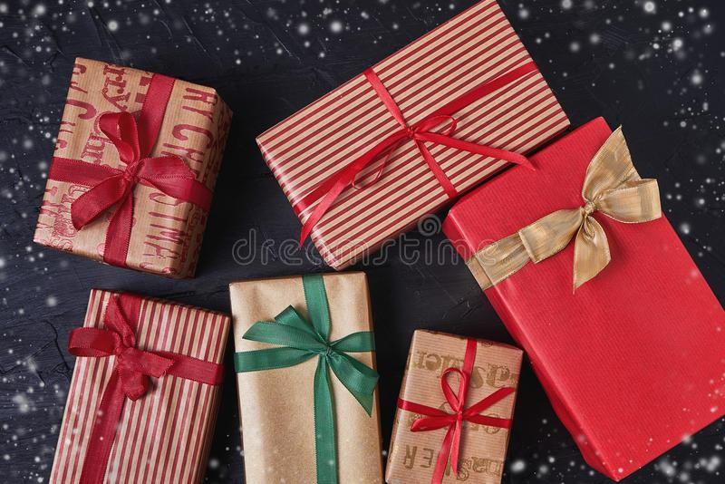 Wrapped gifts boxes decorated with ribbon on black wooden background. Copy space, top view stock images