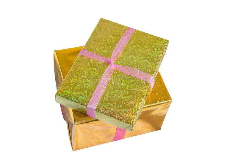 Wrapped in gold foil, two gift boxes tied with red ribbon and stacked, isolated on a white background royalty free stock photos