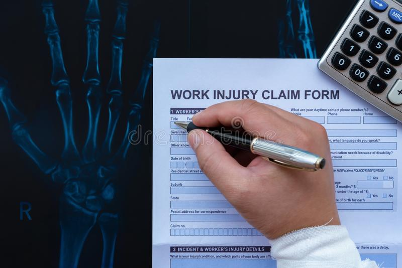 Wrapped hand filling up a work injury claim form with a calculator on top of X-ray film medical and insurance concept stock photos