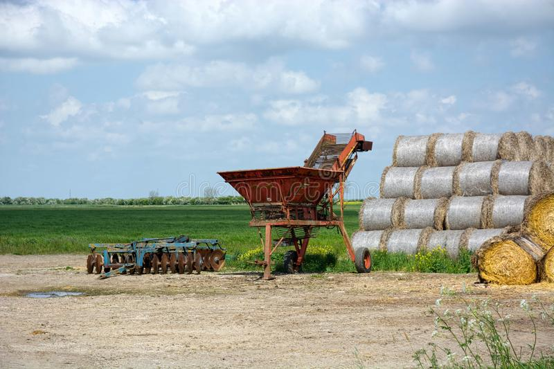 Farm machinery and hay bales outdoors. Wrapped Hay bales in the open with an old plough and machinery nearby on agricultural land stock photo