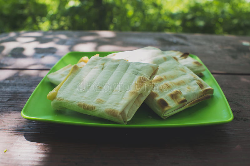 Wrapped pita bread. On a green plate royalty free stock images