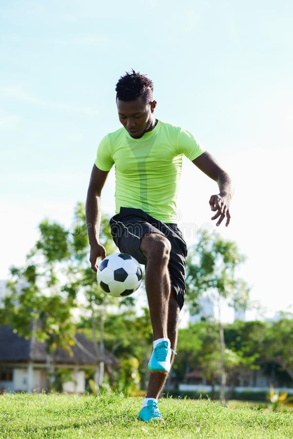 Wrapped up in Soccer Training. Full length portrait of confident Nigerian sportsman wrapped up in soccer training, spacious field and cloudless sky on background stock photography