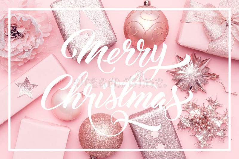 Wrapped xmas boxes, christmas ornaments and baubles. Pink christmas gifts isolated on pastel pink background. royalty free stock photo