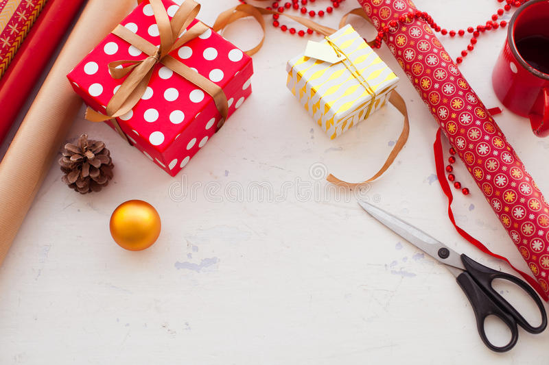 Wrapping Christmas gift - preparation. Accessories on wooden white desk royalty free stock images