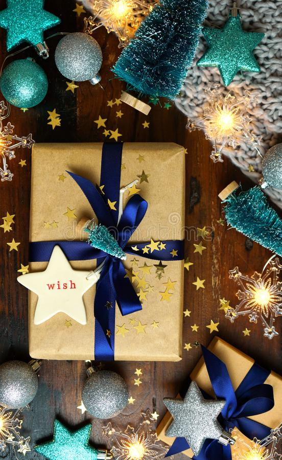 Wrapping Christmas holiday blue gifts on dark wood table, nightime flat lay. royalty free stock images