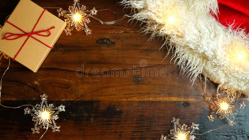 Wrapping Christmas holiday gifts on dark wood table, nightime flat lay. stock photo