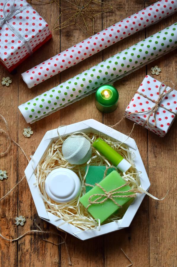 Wrapping cosmetic gift - body cream, bath bomb, soap, lipstick. Composition with present box, packing paper, festive decoration stock photos
