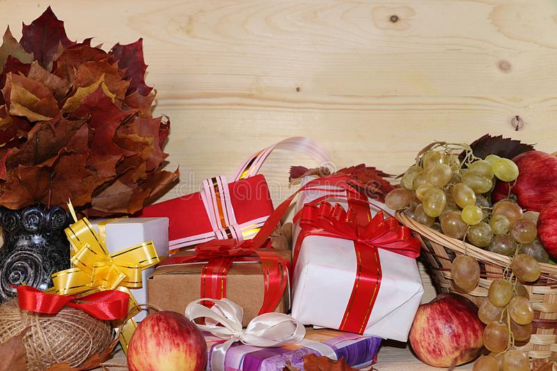 Wrapping day gift, autumn background with seasonal autumn nature berries, pumpkins, apples, grapes and gifts on wooden background. Copy space. Happy stock photo
