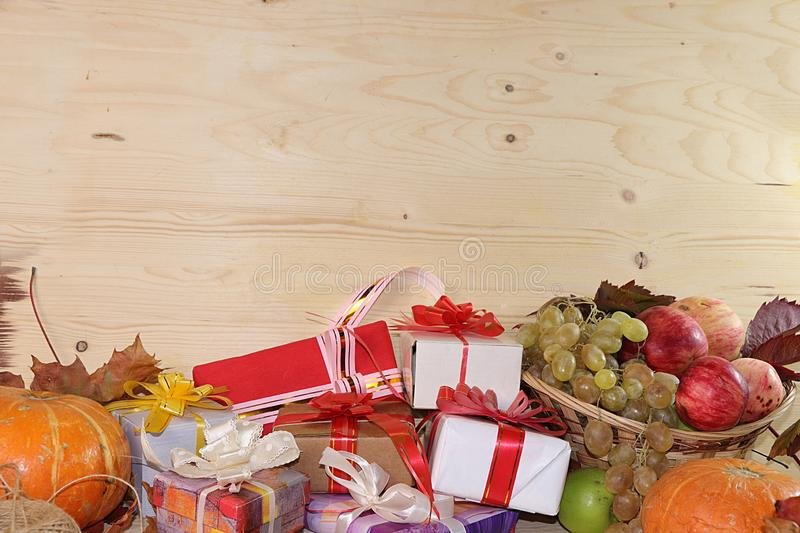 Wrapping day gift, autumn background with seasonal autumn nature berries, pumpkins, apples, grapes and gifts on wooden background. Copy space. Happy royalty free stock photography