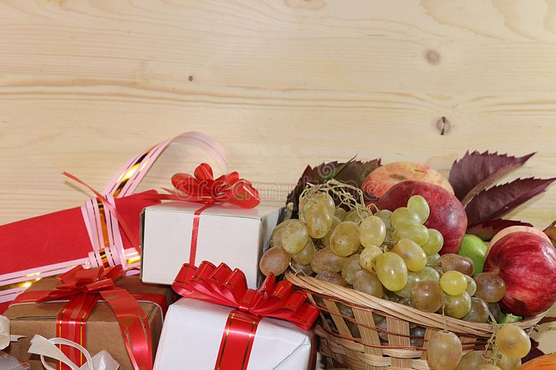 Wrapping day gift, autumn background with seasonal autumn nature berries, pumpkins, apples, grapes and gifts on wooden background. Copy space. Happy stock photos