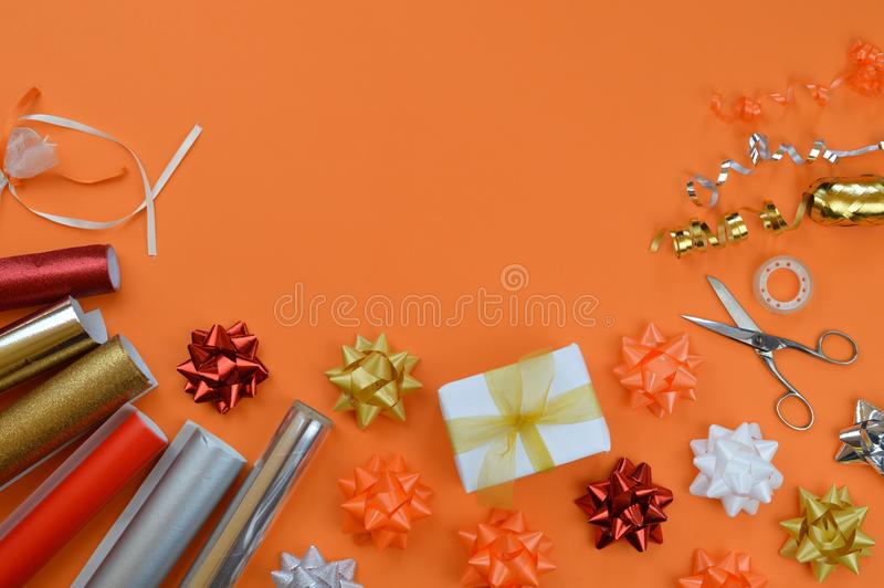 Gift wrapping utensils on orange ground royalty free stock photography