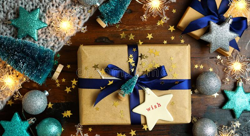 Wrapping Christmas holiday blue gifts on dark wood table, nightime flat lay. royalty free stock image