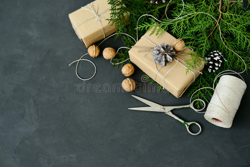 Wrapping rustic eco Christmas packages with brown paper, string and natural fir branches on dark background royalty free stock images