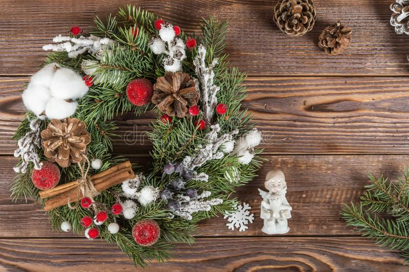 Wreath. Christmas winter frame on dark wooden background. The figure of a little angel with a bear in his hands. Christmas decorat stock photography