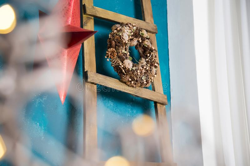 The wreath from cones hangs on the ladder put to a blue wall royalty free stock photo