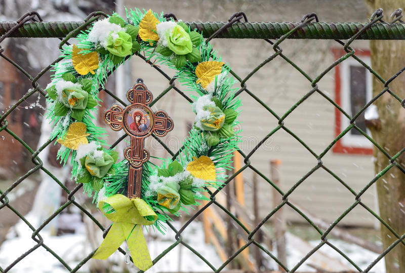 Wreath with a cross and the image of the Mother of God on the fence at home in the Carpathian Mountains. Yaremche, Ukraine royalty free stock images