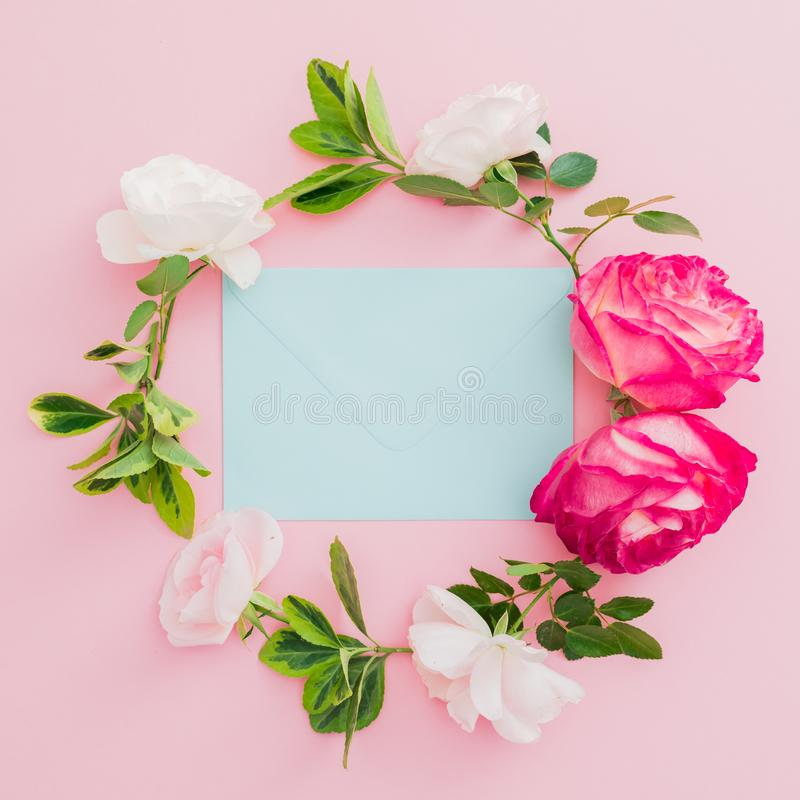 Wreath floral frame with white and red roses flowers and blue envelope on pink background. Flat lay, top view royalty free stock image