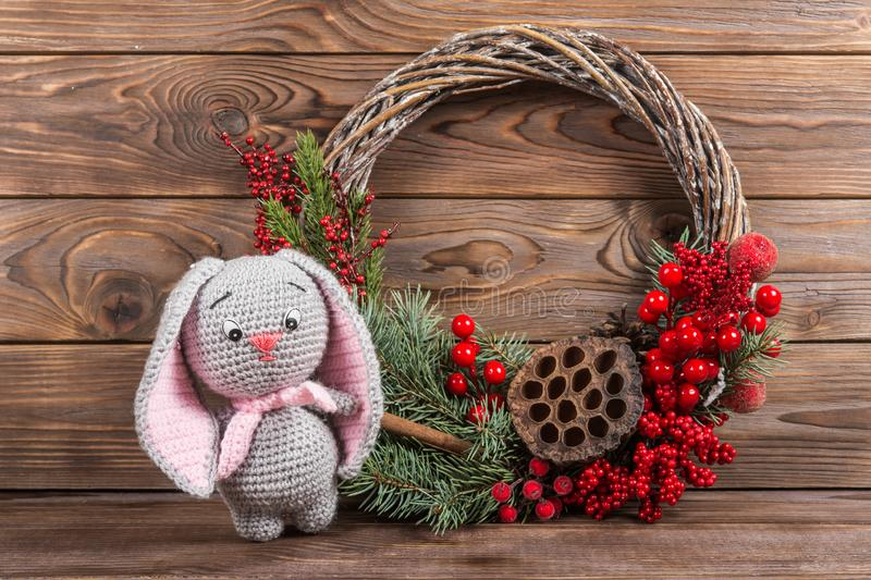 Wreath and hare rabbit. Christmas winter frame on dark wooden background. Red elements Crochet Kraft Toys royalty free stock image