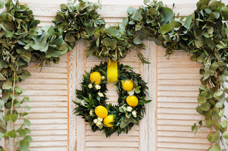 Wreath made of laurel leaves, roses and lemons. As decoration on wooden background stock image