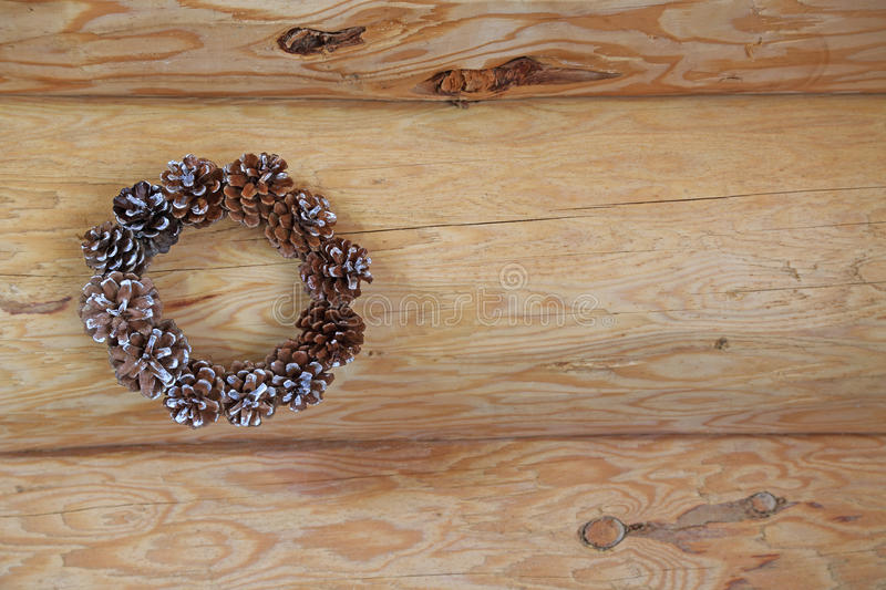 Wreath made of pine cone on a log wall royalty free stock images