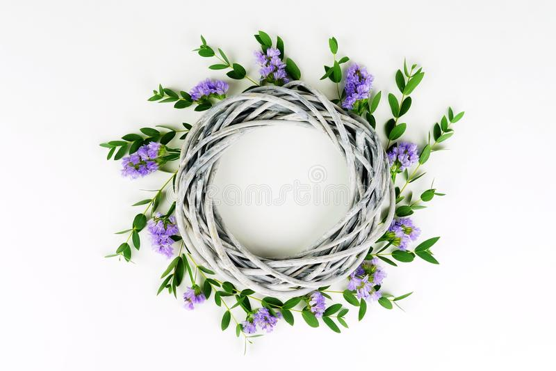 Wreath made of wicker circle, the branches of eucalyptus and purple flowers stock photography
