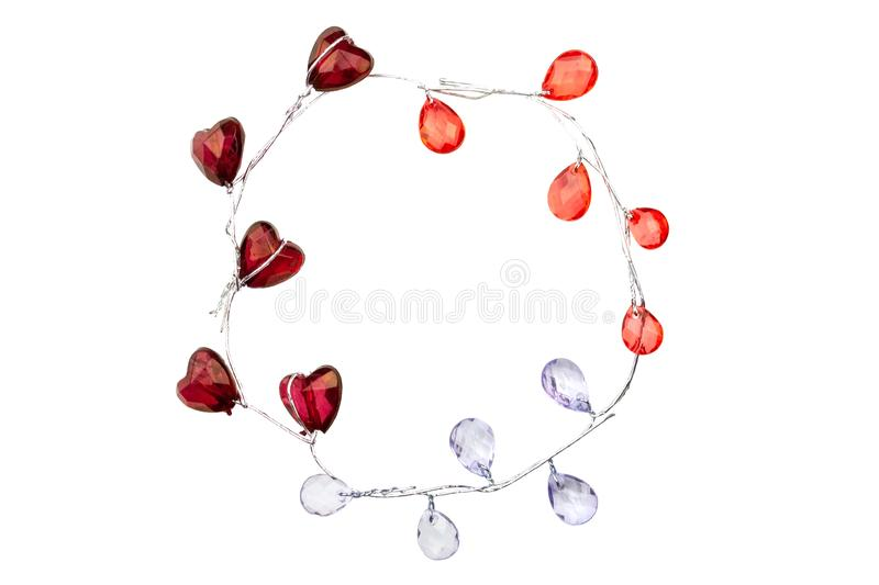 A wreath of silver sprigs with glass burgundy hearts, red and purple droplets isolated on white background.  royalty free stock photos