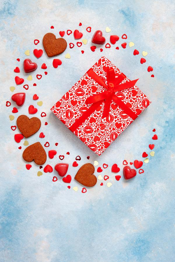 Wreath of sweets, cookies and heart figurines with gift box on blue background. Concept for Valentine`s Day, March 8th and other stock photo