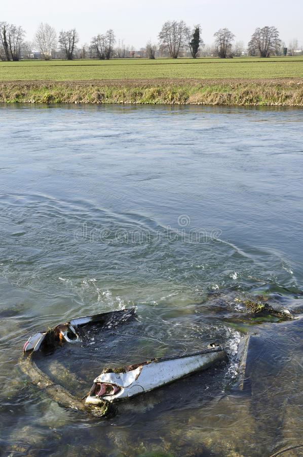 Wreck in muzza canal. Foreshortening of car wreck abandoned in important artificial canal in winter country , shot in bright light on lombardy plains stock photos