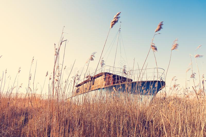 The wreck of a small ship, abandoned on the shore of the Szczecin Lagoon. Vintage effect stock photography