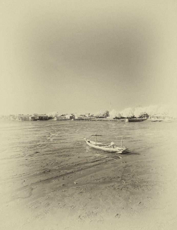 Wrecked boat at receding shore. Taken at Kenjeran beach, Surabaya, east Java, Indonesia royalty free stock photo