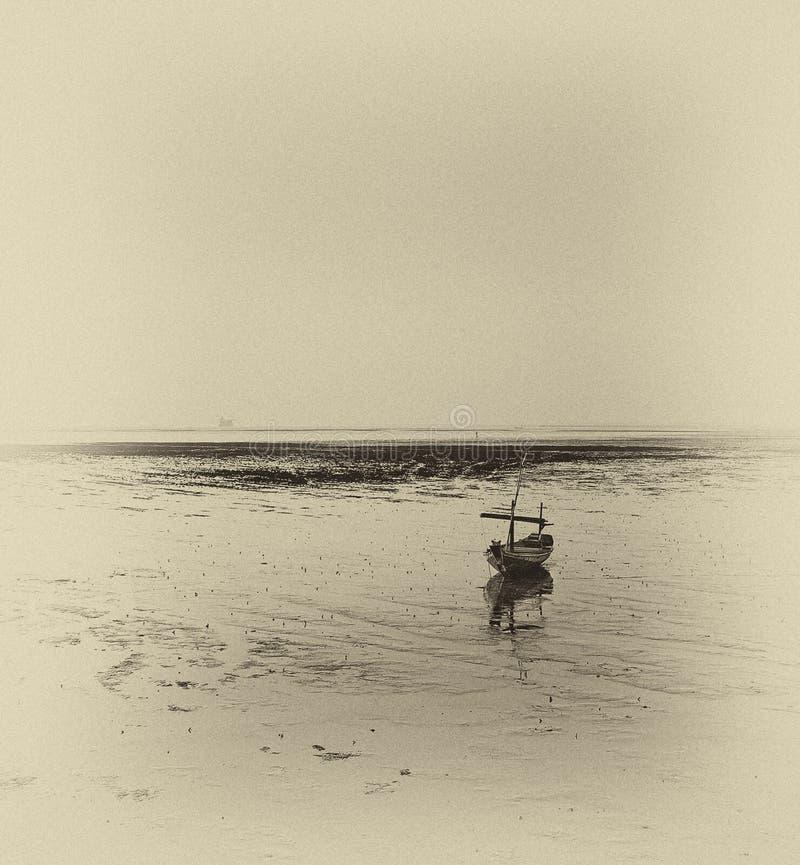 Wrecked boat at receding shore. Taken at Kenjeran beach, Surabaya, east Java, Indonesia royalty free stock photos