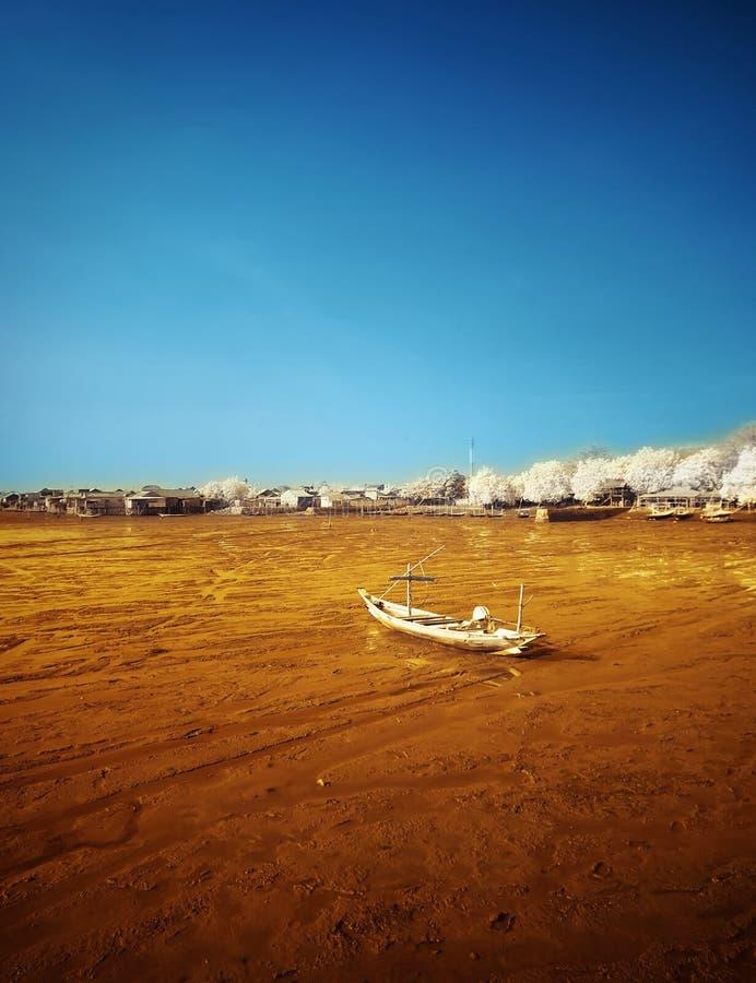 Wrecked boat at receding shore. Taken at Kenjeran beach, Surabaya, east Java, Indonesia royalty free stock images