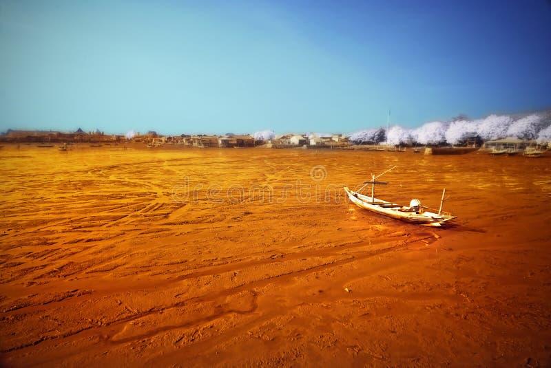 Wrecked boat at receding shore. Taken at Kenjeran beach, Surabaya, east Java, Indonesia royalty free stock image