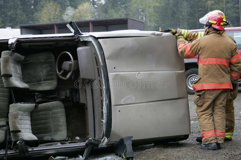 Wrecked Car. Two firefighters standing beside wrecked car tilted on side royalty free stock image