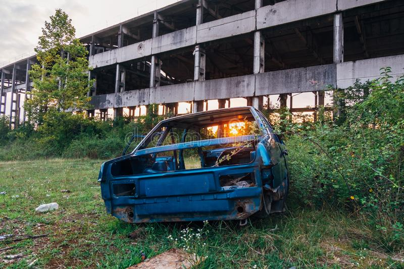 Wrecked car and abandoned ruined industrial building on sunset background.  stock image