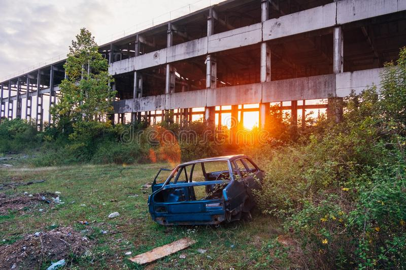 Wrecked car and abandoned ruined industrial building on sunset background.  royalty free stock photography
