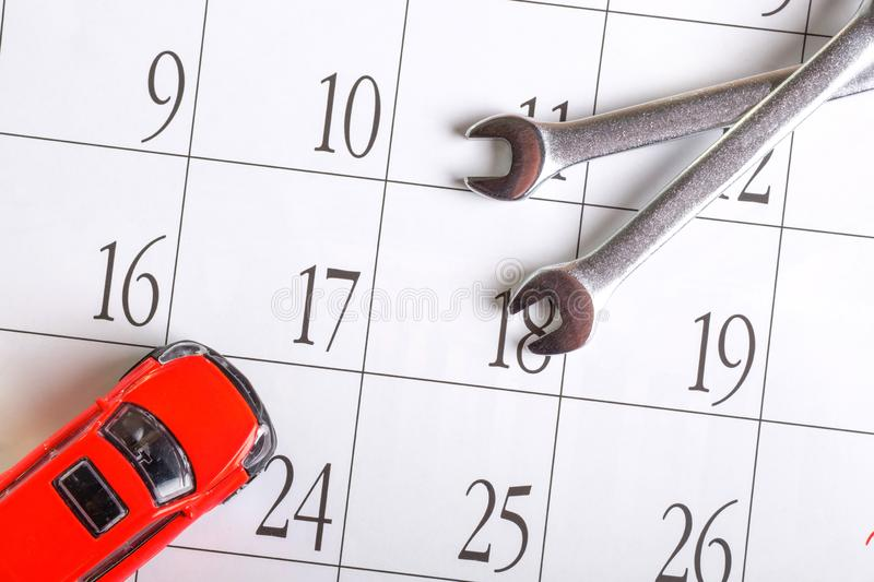 Wrench and car red on the calendar sheet with numbers. Vehicle inspection according to the regular calendar stock images