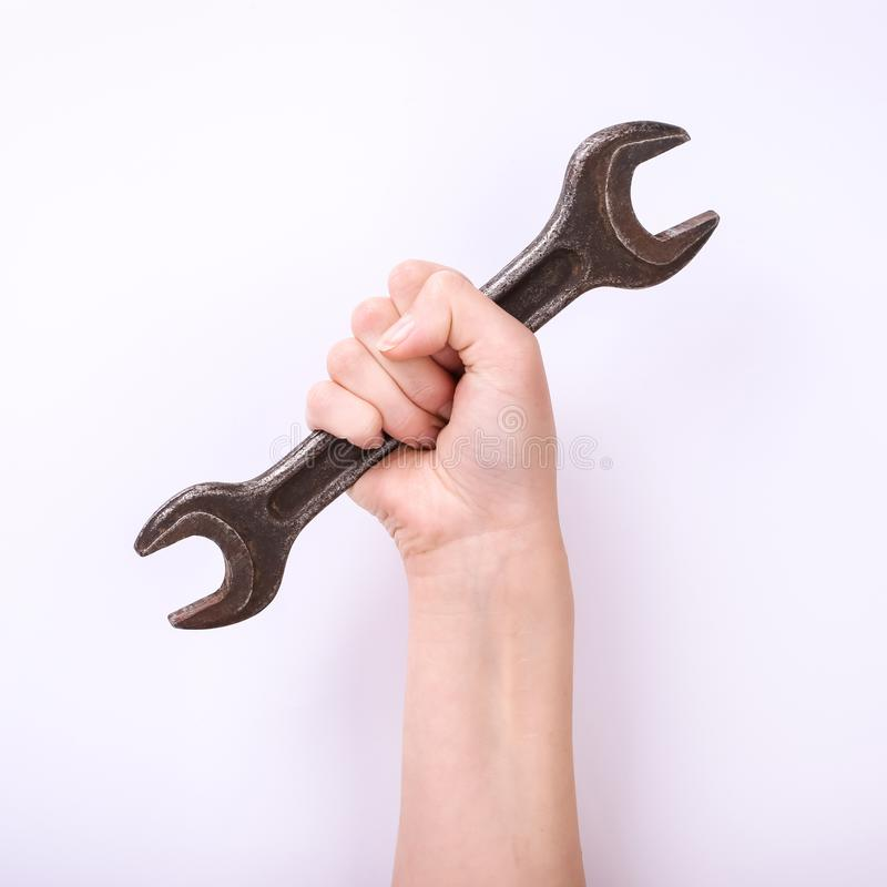 A wrench in the hand of a girl. Symbol of hard work, feminism and labor day. Isolate on white background. A wrench in the hand of a girl. Symbol of hard work royalty free stock photography