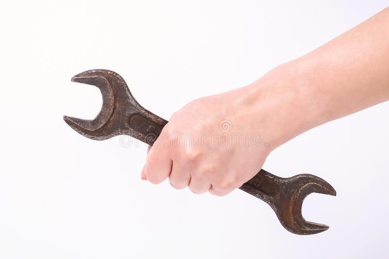 A wrench in the hand of a girl. Symbol of hard work, feminism and labor day. Isolate on white background. A wrench in the hand of a girl. Symbol of hard work stock photography