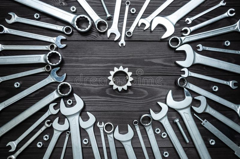 Wrenches gear and heart on dark wooden background. Concept love for your work. Wrenches gear and a heart on a dark wooden background. Concept love for your work stock images