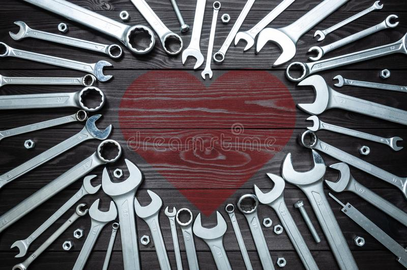 Wrenches and heart on dark wooden background. Concept love for your work. Wrenches and a heart on a dark wooden background. Concept love for their work stock photography