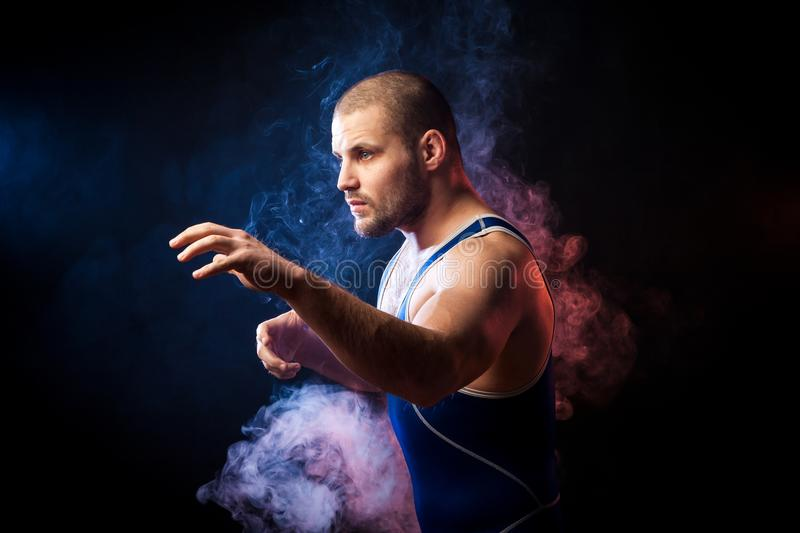 Wresler posing on black. A young sporty man wrestler in a green sports shirt and blue wrestling tights posing against a blue and red vape smoke background on a stock photography