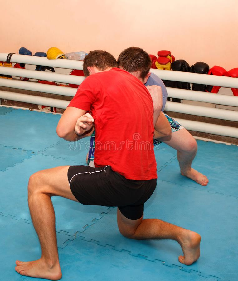 Grapple. Two wrestlers in the underground gym. Wrestlers doing grapple. Two strong men in the underground gym royalty free stock photography