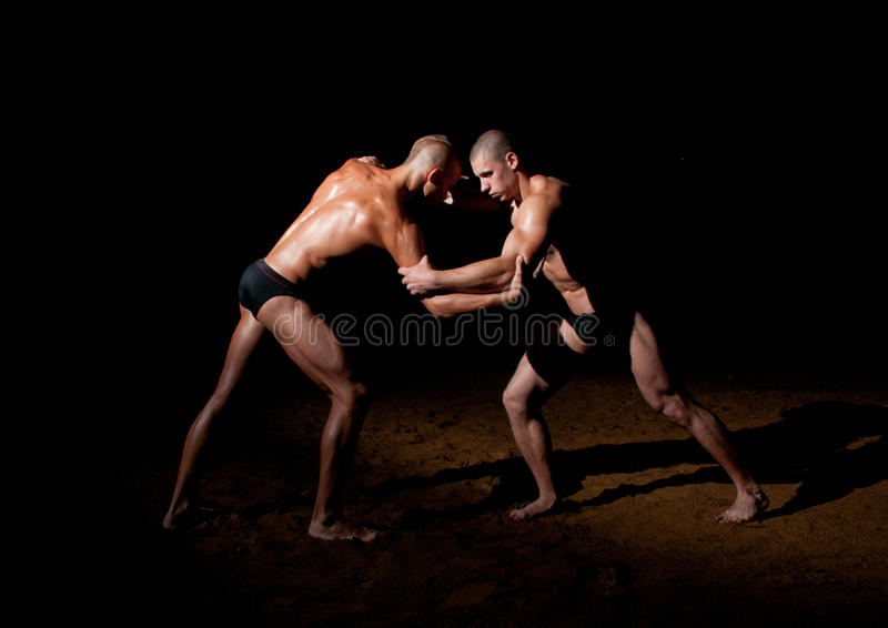 Wrestling models. Two male models wrestling in the sand royalty free stock images