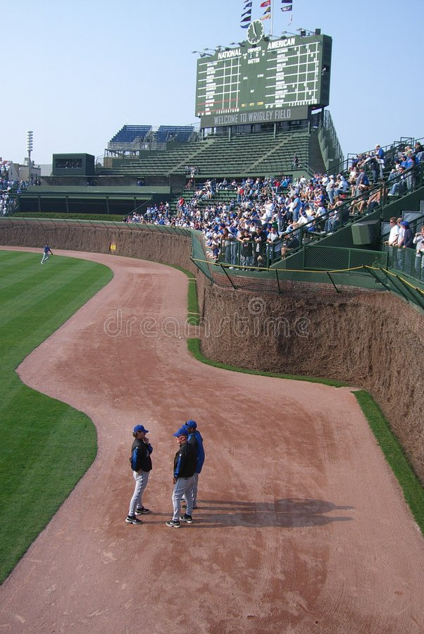 Wrigley Field - Chicago Cubs Ivy and Scoreboard. Players gather by famous Ivy Wall at Wrigley Field, home of the Chicago cubs, before a game with the New York stock photo