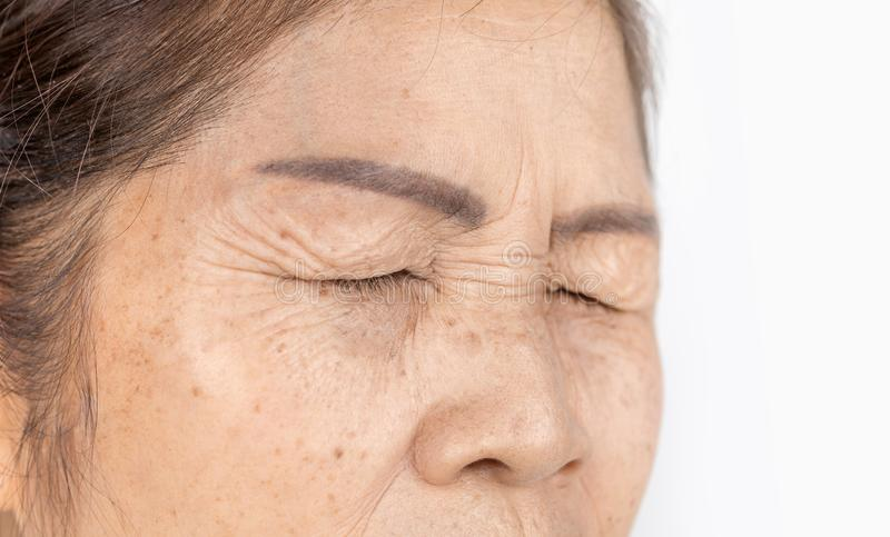 Close up skin wrinkle and freckles of old asian woman face which closing eyes. Wrinkle freckles and skin line on close up elderly asian woman face 60-70 years stock images