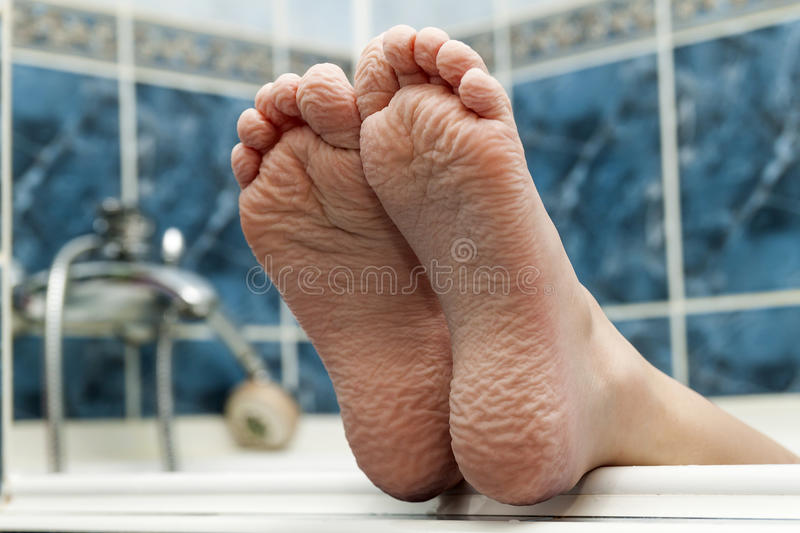 Wrinkled bare feet coming out from a bathtub. Young person getting a bath feet close-up indoor in bathroom interrior photo stock image